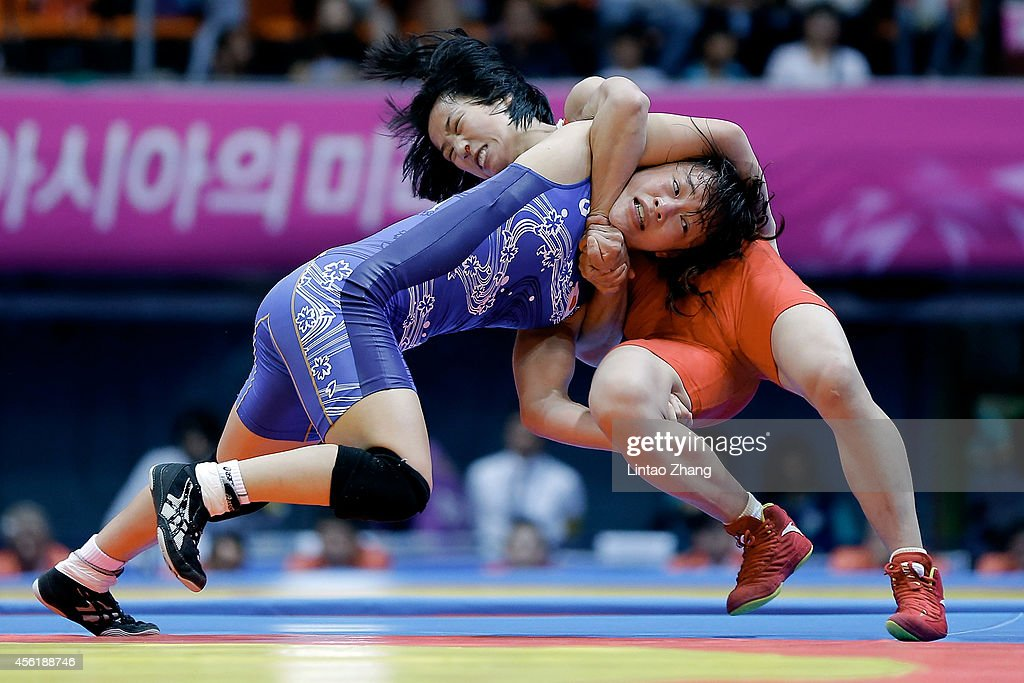 Eri Tosaka (blue) of Japan competes with Sun Yanan of China (red) in the Wrestling Women's Freestyle 48 kg Gold Medal Final during day eight of the 2014 Asian Games at Dowon Gymnasium on September 27, 2014 in Incheon, South Korea.