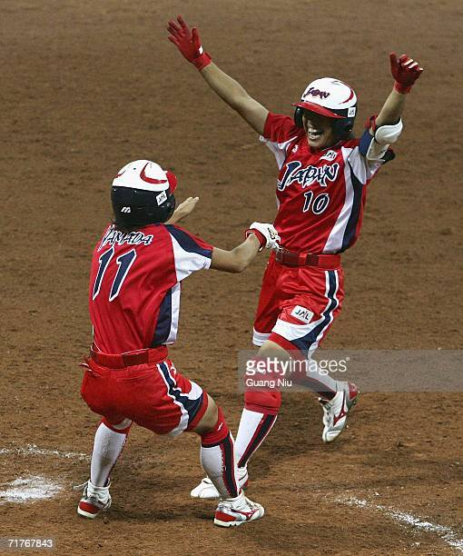 Eri Yamada and Sachiko Ito of Japan celebrate after they won the match 21 against Australia during ISF XI Women's Fast Pitch Softball World...