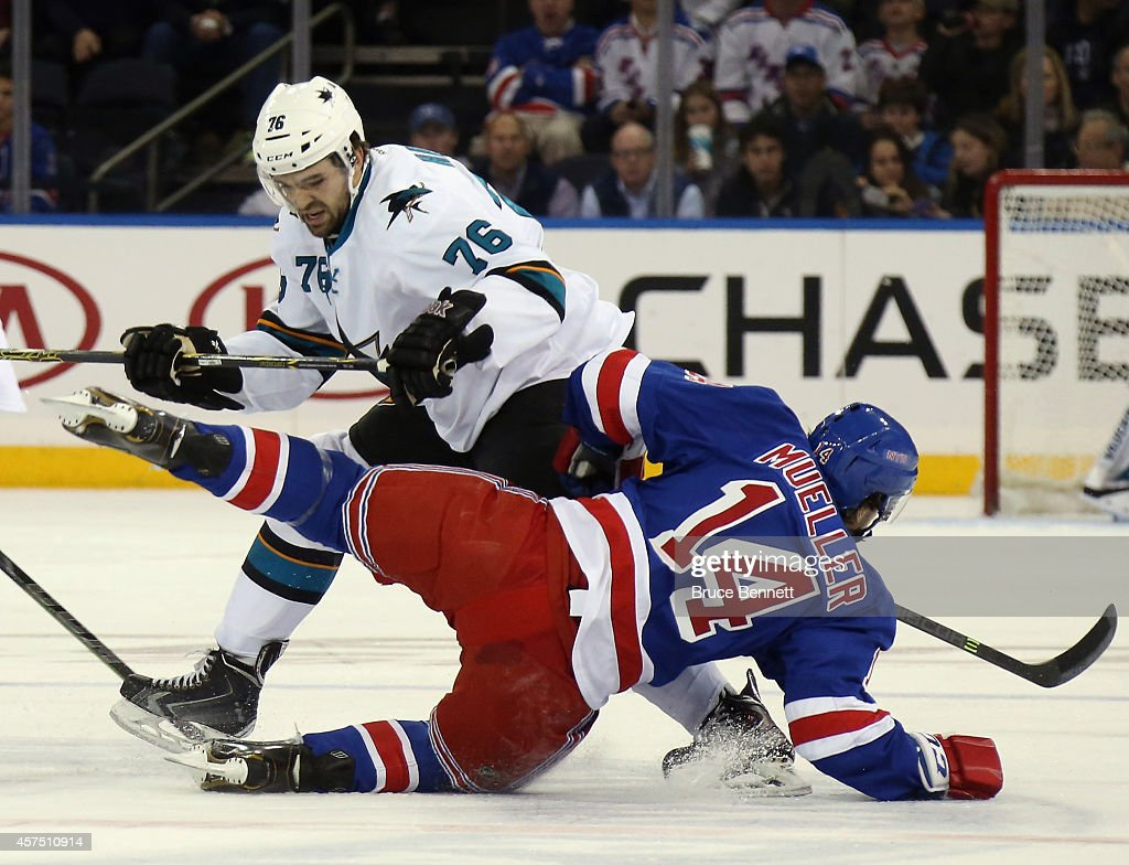 Eriah Hayes of the San Jose Sharks checks Chris Mueller of the New York Rangers to the ice during the first period at Madison Square Garden on...