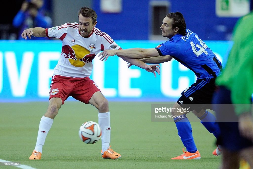 Eric Alexander #12 of the New York RedBulls and Heath Pearce #44 of the Montreal Impact battle for the ball during the MLS game at the Olympic Stadium on April 5, 2014 in Montreal, Quebec, Canada.