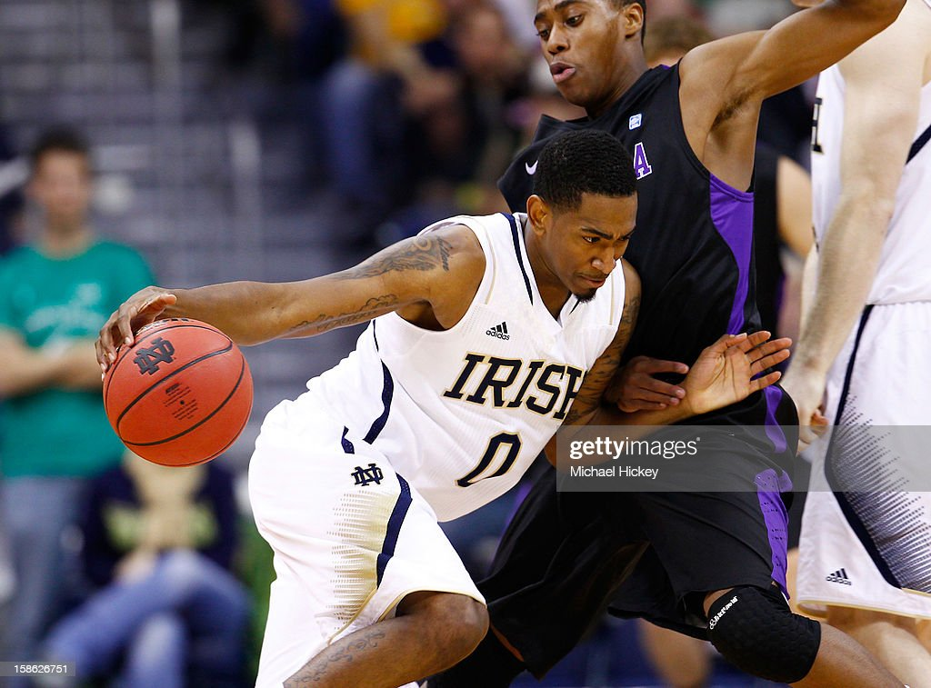 Eric Atkins #0 of the Notre Dame Fighting Irish dribbles against Tahjere McCall #5 of the Niagara Purple Eagles at Purcel Pavilion on December 21, 2012 in South Bend, Indiana.