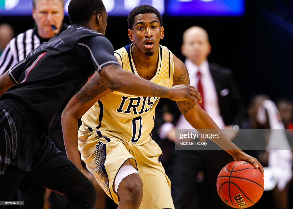<a gi-track='captionPersonalityLinkClicked' href=/galleries/search?phrase=Eric+Atkins&family=editorial&specificpeople=7379862 ng-click='$event.stopPropagation()'>Eric Atkins</a> #0 of the Notre Dame Fighting Irish dribbles the ball up court as he is guarded by Cashmere Wright #1 of the Cincinnati Bearcats at Purcel Pavilion on February 24, 2013 in South Bend, Indiana. Notre Dame defeated Cincinnati 62-41.