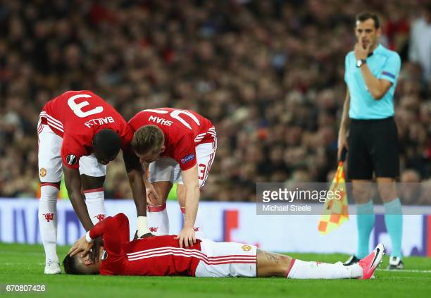 Eric Bailly and Luke Shaw stand over injured team mate Marcos Rojo of Manchester United during the UEFA Europa League quarter final second leg match...