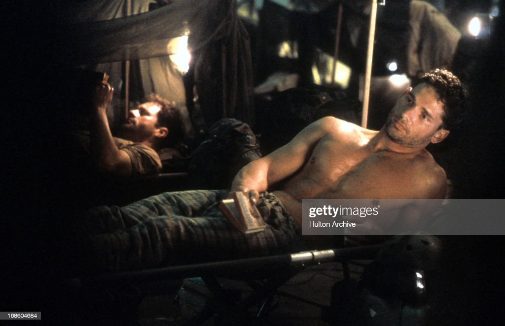 Eric Bana laying shirtless on a cot in the barracks in a scene from the film 'Black Hawk Down', 2001.