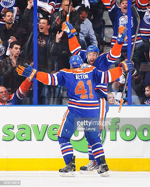 Eric Belanger of the Edmonton Oilers celebrates scoring the Oilers' first goal against the Winnipeg Jets along with teammate Will Acton during an NHL...