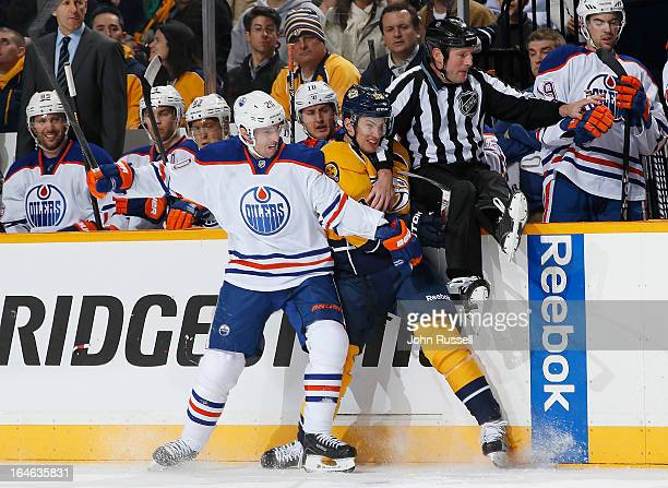 Eric Belanger of the Edmonton Oilers checks Roman Josi of the Nashville Predators into linesman Don Henderson during an NHL game at the Bridgestone...