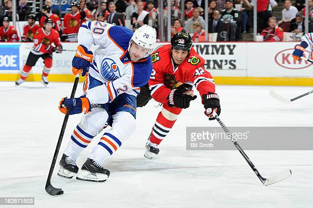Eric Belanger of the Edmonton Oilers skates with the puck as Michal Rozsival of the Chicago Blackhawks reaches from behind during the NHL game on...