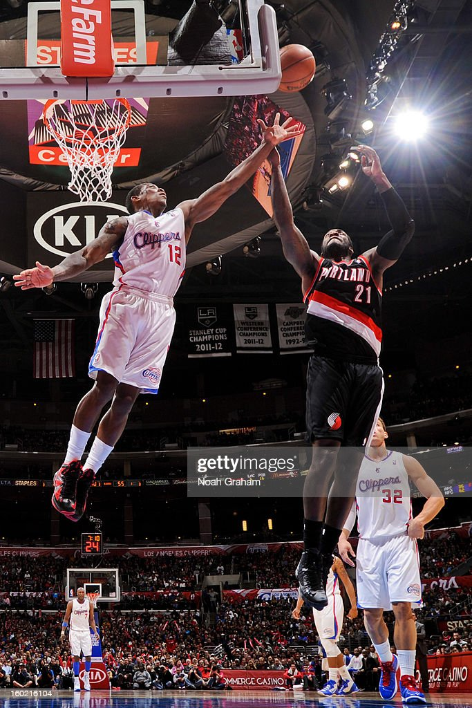 Eric Bledsoe #12 of the Los Angeles Clippers and J.J. Hickson #21 of the Portland Trail Blazers reach for a rebound during their game at Staples Center on January 27, 2013 in Los Angeles, California.