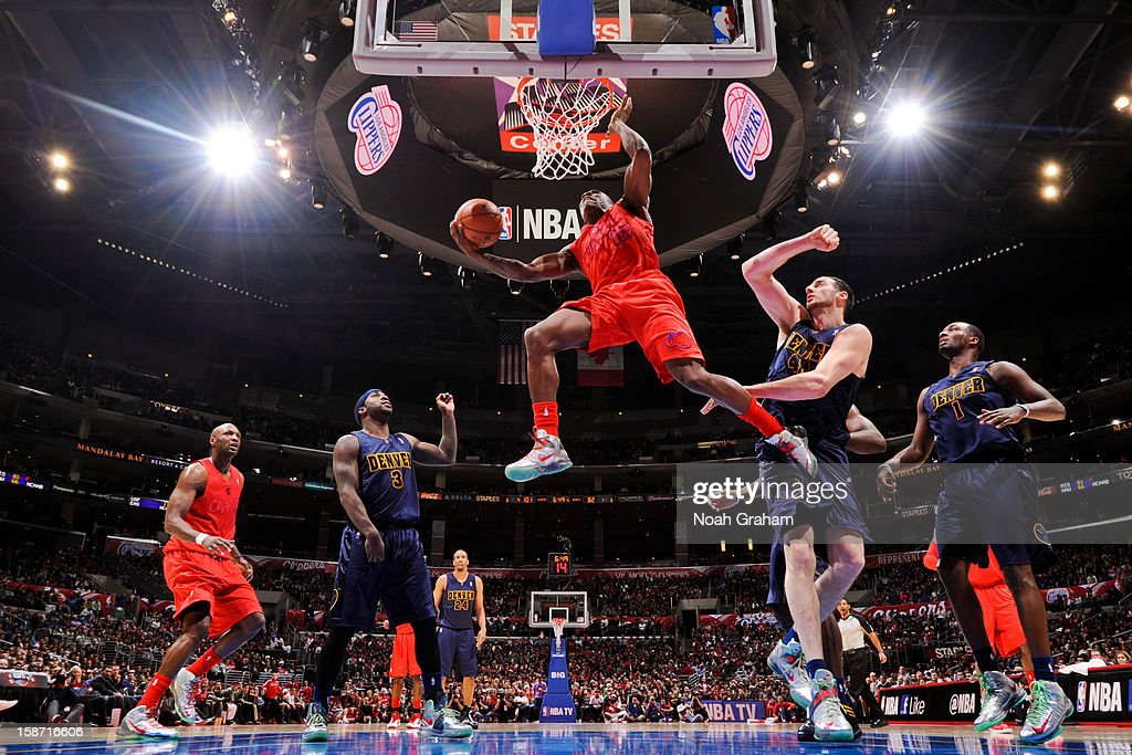 Eric Bledsoe #12 of the Los Angeles Clippers drives to the basket against Kosta Koufos #41 and Ty Lawson #3 of the Denver Nuggets during a Christmas Day game at Staples Center on December 25, 2012 in Los Angeles, California.