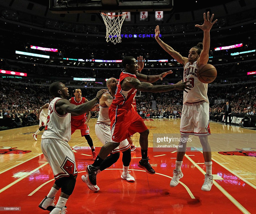 Eric Bledsoe #12 of the Los Angeles Clippers passes under pressure from L-R) Nate Robinson #2, Carlos Boozer #5 and Joakim Noah #13 of the Chicago Bulls at the United Center on December 11, 2012 in Chicago, Illinois. The Clippers defeated the Bulls 94-89.