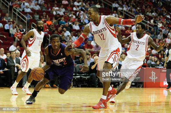 Eric Bledsoe of the Phoenix Suns dribbles past Dwight Howard of the Houston Rockets during the game at Toyota Center on December 4 2013 in Houston...