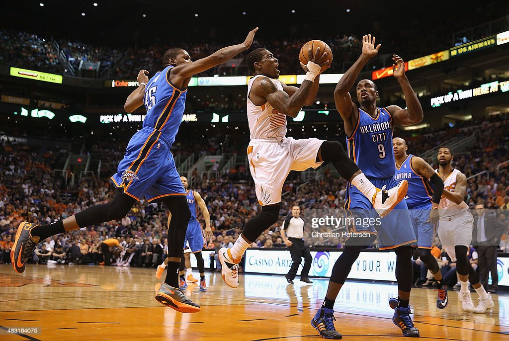 Eric Bledsoe #2 of the Phoenix Suns drives to the basket past Kevin Durant #35 and Serge Ibaka #9 of the Oklahoma City Thunder during the second half of the NBA game at US Airways Center on April 6, 2014 in Phoenix, Arizona. The Suns defeated the Thunder 122-115.