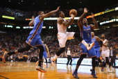 Eric Bledsoe of the Phoenix Suns drives to the basket past Kevin Durant and Serge Ibaka of the Oklahoma City Thunder during the second half of the...