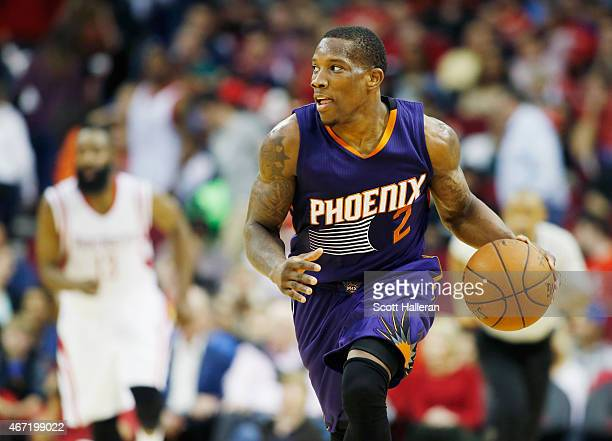 Eric Bledsoe of the Phoenix Suns takes the basketball upcourt as James Harden of the Houston Rockets looks on during their game at the Toyota Center...