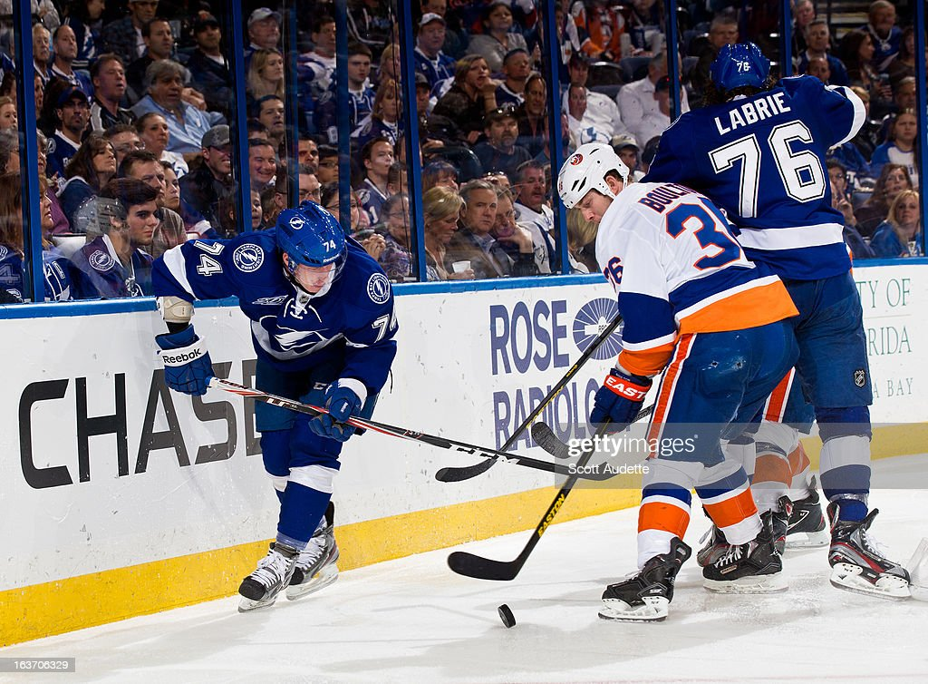 <a gi-track='captionPersonalityLinkClicked' href=/galleries/search?phrase=Eric+Boulton&family=editorial&specificpeople=217746 ng-click='$event.stopPropagation()'>Eric Boulton</a> #36 of the New York Islanders fights for control of the puck with Ondrej Palat #74 of the Tampa Bay Lightning during the third period of the game at the Tampa Bay Times Forum on March 14, 2013 in Tampa, Florida.