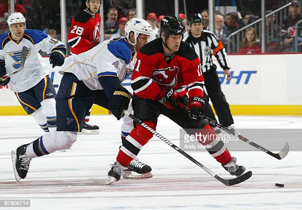 Eric Brewer of the St Louis Blues and Dean McAmmond of the New Jersey Devils pursue a loose puck during the game at the Prudential Center on March 20...