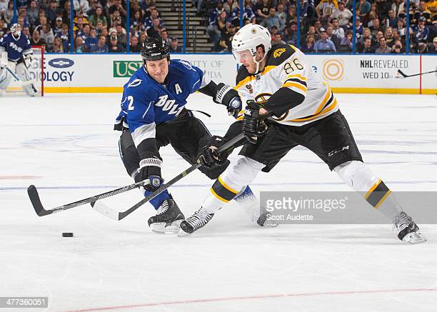 Eric Brewer of the Tampa Bay Lightning battles for the puck against Kevan Miller of the Boston Bruins during the third period at the Tampa Bay Times...