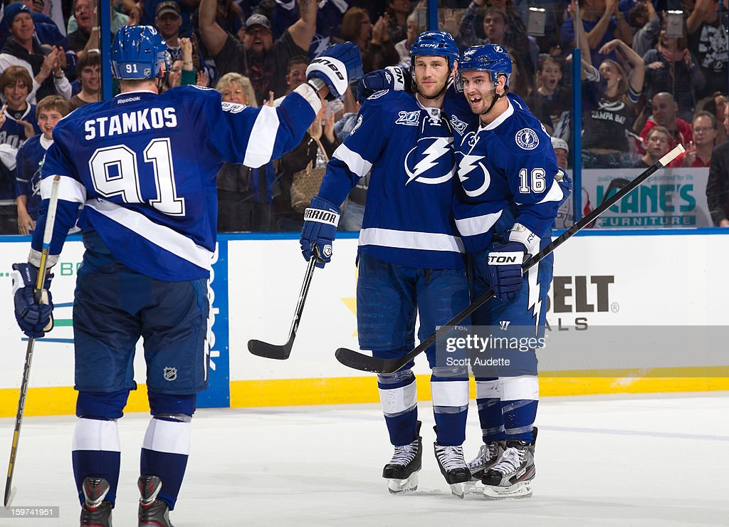 <a gi-track='captionPersonalityLinkClicked' href=/galleries/search?phrase=Eric+Brewer&family=editorial&specificpeople=202144 ng-click='$event.stopPropagation()'>Eric Brewer</a> #2 of the Tampa Bay Lightning celebrates his goal with teammates <a gi-track='captionPersonalityLinkClicked' href=/galleries/search?phrase=Teddy+Purcell&family=editorial&specificpeople=4537302 ng-click='$event.stopPropagation()'>Teddy Purcell</a> #16 and <a gi-track='captionPersonalityLinkClicked' href=/galleries/search?phrase=Steven+Stamkos&family=editorial&specificpeople=4047623 ng-click='$event.stopPropagation()'>Steven Stamkos</a> #91during the third period against the Washington Capitals at the Tampa Bay Times Forum on January 19, 2013 in Tampa, Florida. The Tampa Bay Lightning won 6-3 against the Washington Capitals.