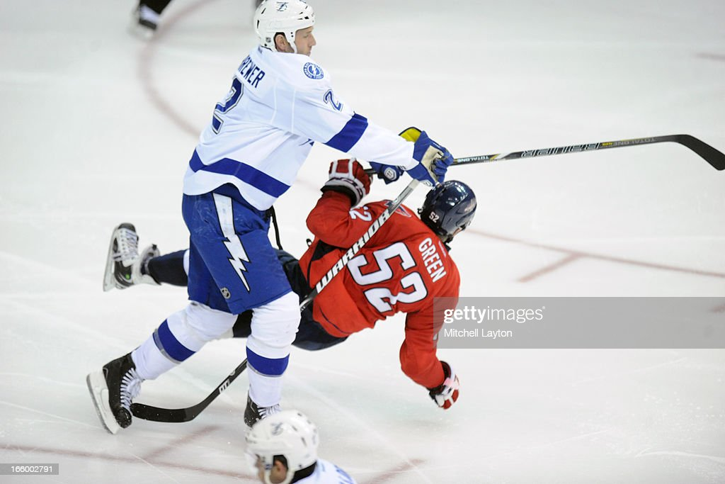 <a gi-track='captionPersonalityLinkClicked' href=/galleries/search?phrase=Eric+Brewer&family=editorial&specificpeople=202144 ng-click='$event.stopPropagation()'>Eric Brewer</a> #2 of the Tampa Bay Lightning puts a hit on Mike Green #52 of the Washington Capitals during an NHL hockey game on April 7, 2013 at the Verizon Center in Washington, DC.