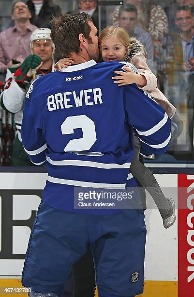 Eric Brewer of the Toronto Maple Leafs receives recognition from his youngest daughter for playing 1000 NHL games prior to play between the Minnesota...