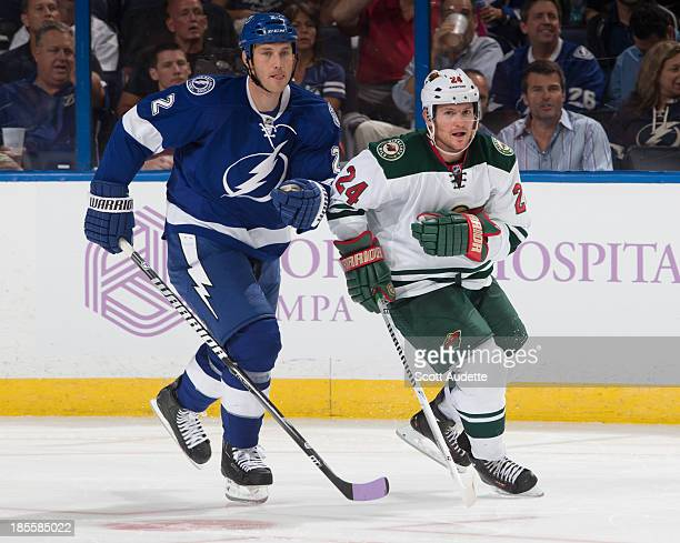Eric Brewern of the Tampa Bay Lightning and Matt Cooke of the Minnesota Wild watch the play at the Tampa Bay Times Forum on October 17 2013 in Tampa...