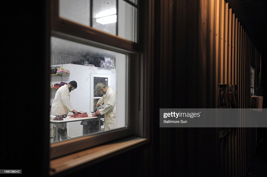 Eric Brown, left, and Justin Foster are framed in the window as they butcher a deer at Back 40 Farm, December 6, 2012. The Back 40 Deer Processing butchers and processes donated deer, which is used as meat for FHFH member agencies like food banks and church pantries.