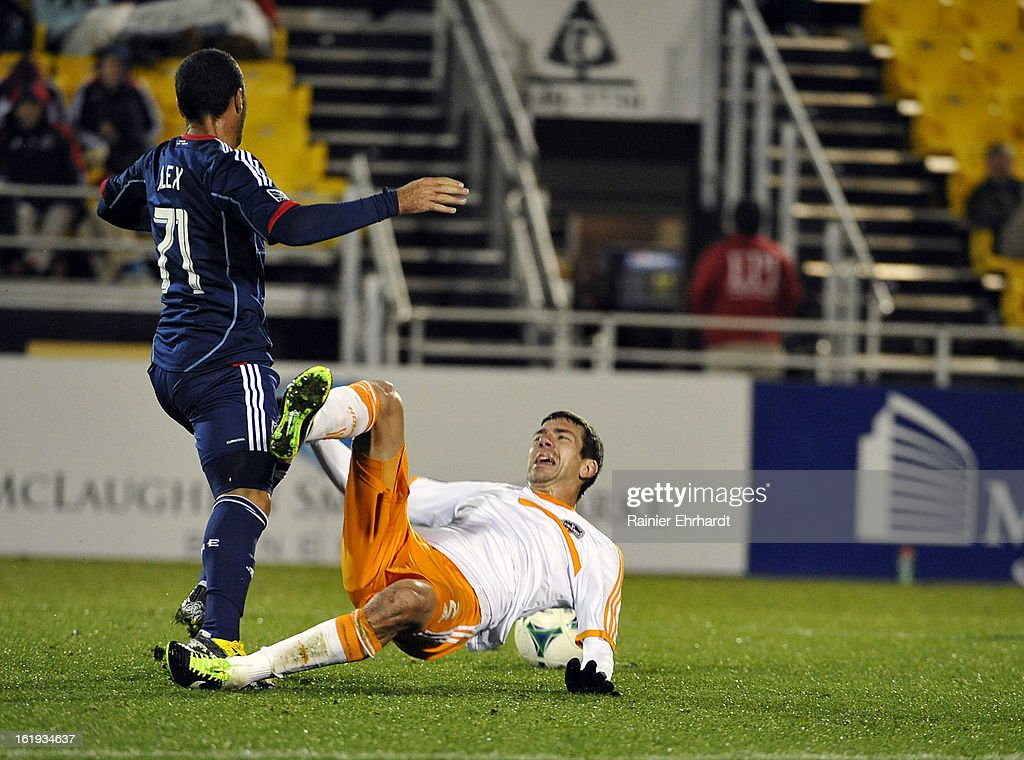 Eric Brunner #2 of the Houston Dynamo falls to the ground as Alex #71 of the Chicago Fire battles for the ball during the second half of their game at Blackbaud Stadium on February 16, 2013 in Charleston, South Carolina.