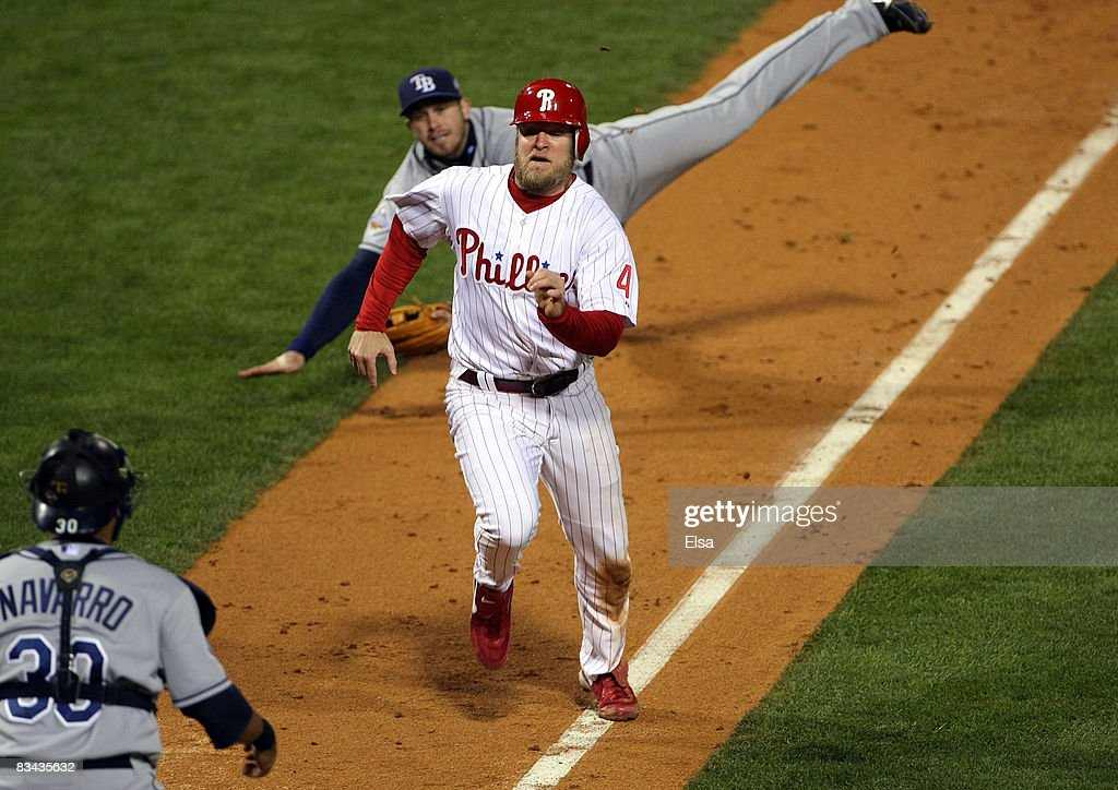 Eric Bruntlett #4 of the Philadelphia Phillies scores the winning run as Evan Longoria #3 of the Tampa Bay Rays tries to flip the ball to Dioner Navarro #30 in game three of the 2008 MLB World Series on October 25, 2008 at Citizens Bank Park in Philadelphia, Pennsylvania.