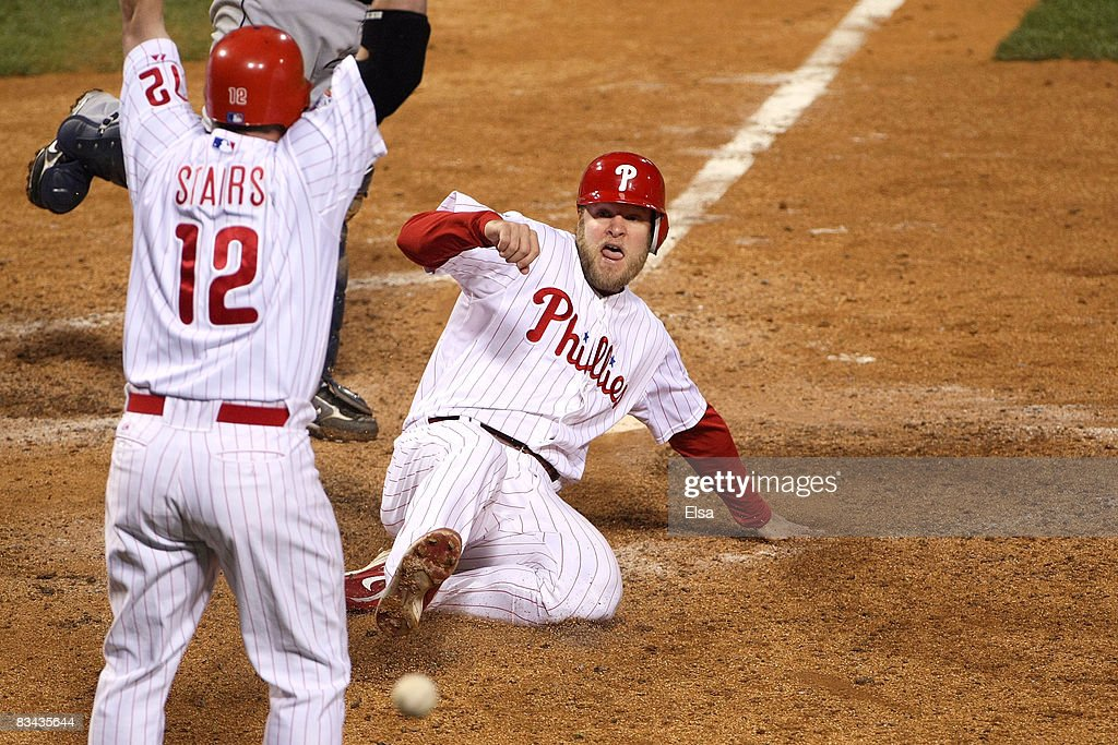 Eric Bruntlett #4 of the Philadelphia Phillies scores the winning run against the Tampa Bay Rays as teammate Matt Stairs #12 looks on in game three of the 2008 MLB World Series on October 25, 2008 at Citizens Bank Park in Philadelphia, Pennsylvania.
