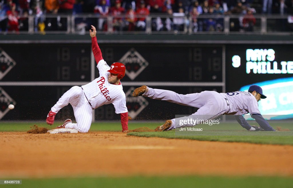 Eric Bruntlett #4 of the Philadelphia Phillies slides into second as Jason Bartlett #8 of the Tampa Bay Rays fails to come up with the ball on a bad throw during game three of the 2008 MLB World Series on October 25, 2008 at Citizens Bank Park in Philadelphia, Pennsylvania.