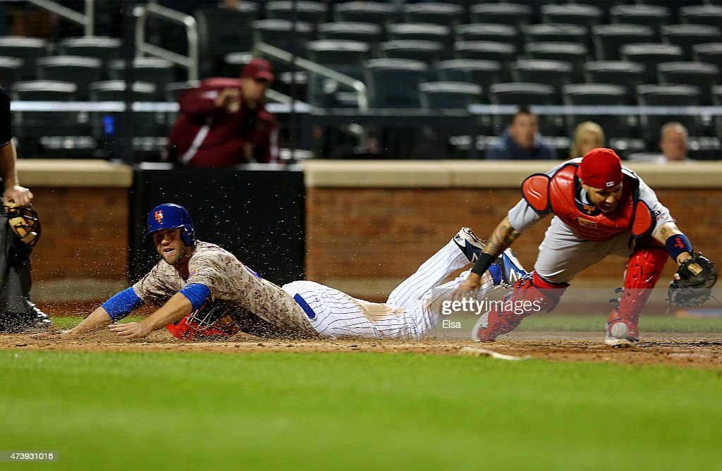 Eric Campbell of the New York Mets scores the game winning run on a hit by John Mayberry Jr #44 of the New York Mets in the 14th inning as Yadier...