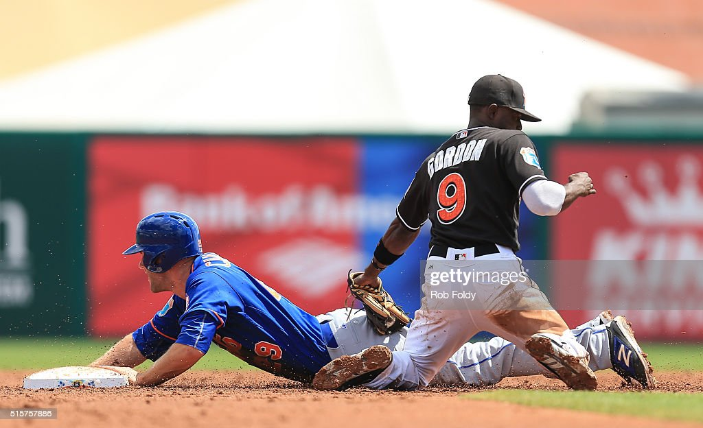 Eric Campbell #29 of the New York Mets slides safely into second base under the tag of Dee Gordon #9 of the Miami Marlins during the spring training game on March 15, 2016 in Jupiter, Florida.