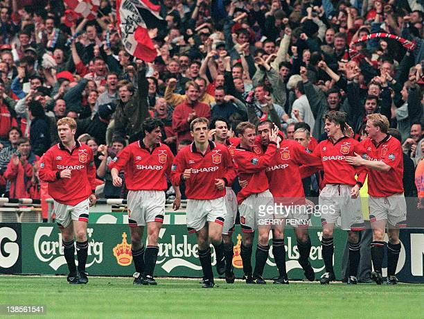 Eric Cantona is congratulated by Manchester United players after scoring the only goal 11 May 1996 at Wembley Stadium in London when he capitained...