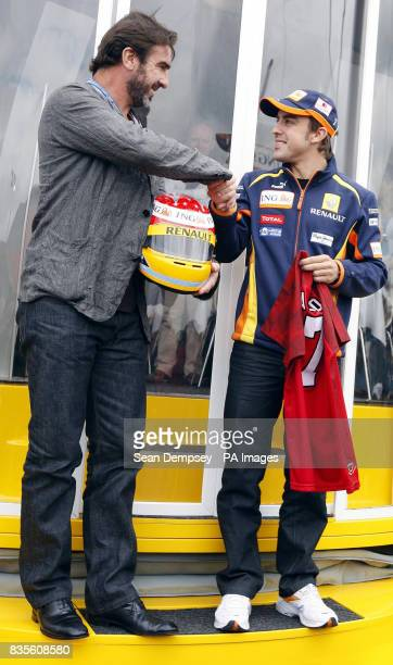 Eric Cantona shakes hands with Renault's Fernando Alonso during a photocall prior to the British Grand Prix at Silverstone Northamptonshire
