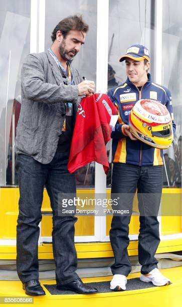 Eric Cantona signs an old Manchester United replica shirt for Renault's Fernando Alonso during a photocall prior to the British Grand Prix at...