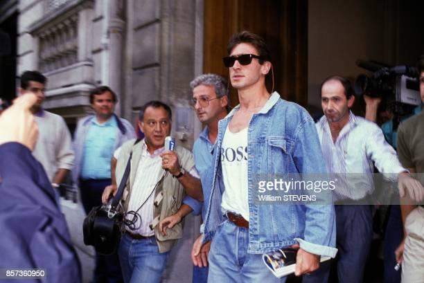 Eric Cantona sortant de la Federation Francaise de Football entoure de journalistes et photographes le 23 aout 1988 a PAris France