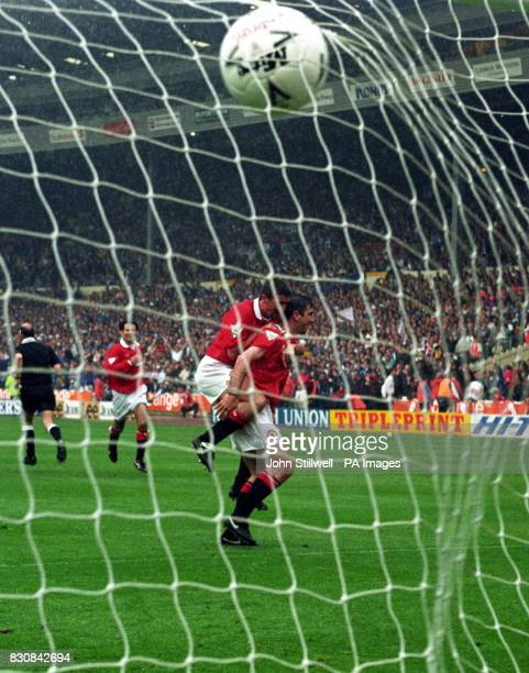 Eric Cantona turns away after scoring Manchester United's goal as teammate Roy Keane jumps on his back during the FA Cup final against Chelsea at...