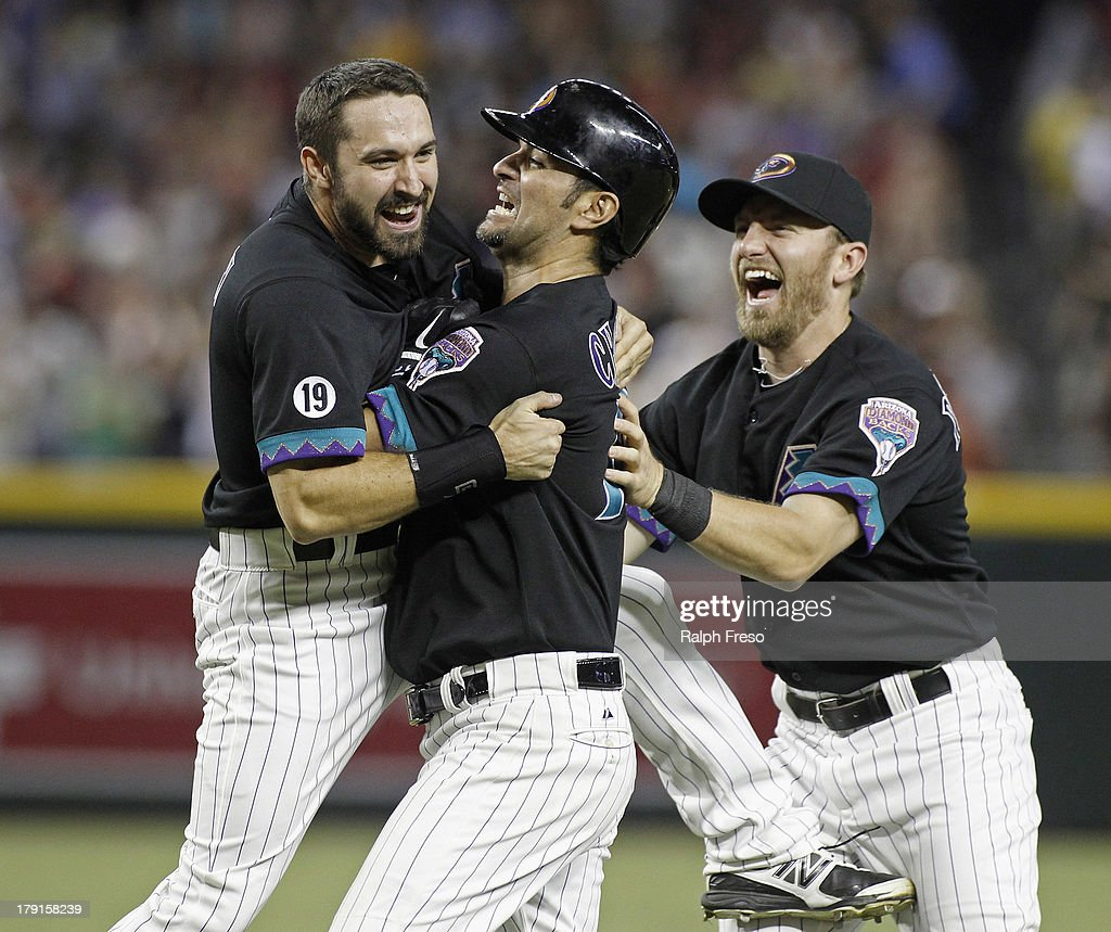 <a gi-track='captionPersonalityLinkClicked' href=/galleries/search?phrase=Eric+Chavez&family=editorial&specificpeople=201561 ng-click='$event.stopPropagation()'>Eric Chavez</a> #12 of the Arizona Diamondbacks (C) celebrates with teammates <a gi-track='captionPersonalityLinkClicked' href=/galleries/search?phrase=Adam+Eaton&family=editorial&specificpeople=210898 ng-click='$event.stopPropagation()'>Adam Eaton</a> #6 (Lt) and Cliff Pennington #4 following his game-winning walk-off RBI single against the San Francisco Giants in the ninth inning of a MLB game at Chase Field on August 31, 2013 in Phoenix, Arizona. The Diamondbacks won the game 4-3.