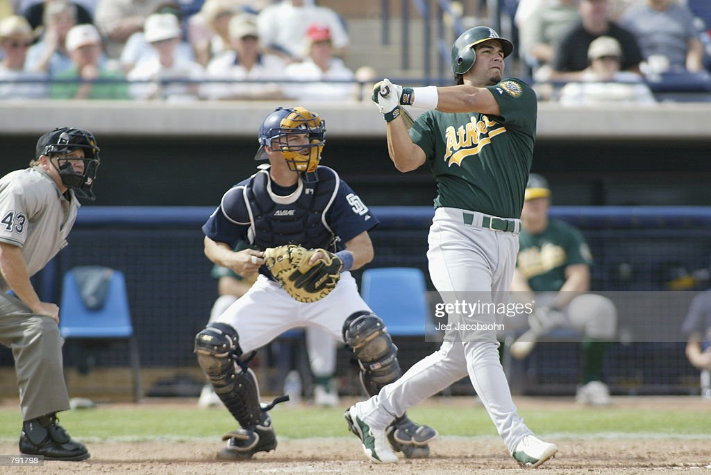 Eric Chavez of the Oakland A's hits a homerun as catcher Tom Lampkin of the San Diego Padres looks on during a Spring Training game oon March 5, 2002 at Peoria Stadium in Peoria, AZ.