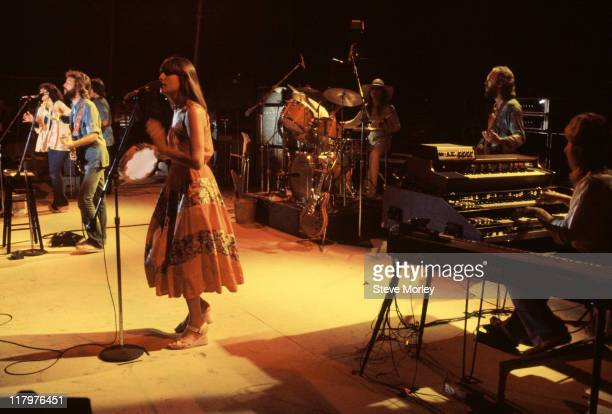 Eric Clapton Britiish singersongwriter and guitarist with backing singers Yvonne Elliman and Marcella Detroit standing either side of him on stage...