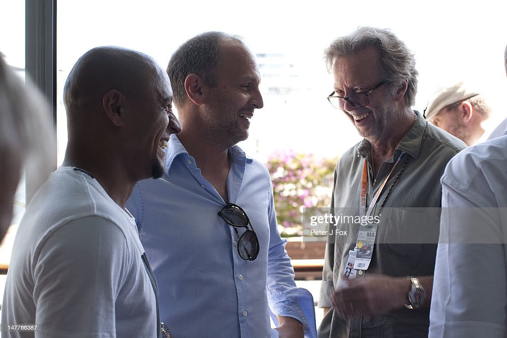 Eric Clapton of Great Britain chats with Roberto Carlos of Brazil during the European Grand Prix at the Valencia Street Circuit on June 24, 2012 in Valencia, Spain.