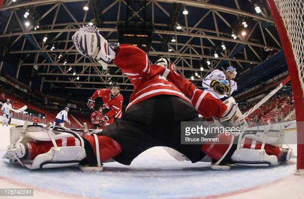 Eric Comrie of Team Canada moves across to make the save on Henri Ikonen of Team Finland during the 2013 USA Hockey Junior Evaluation Camp at the...