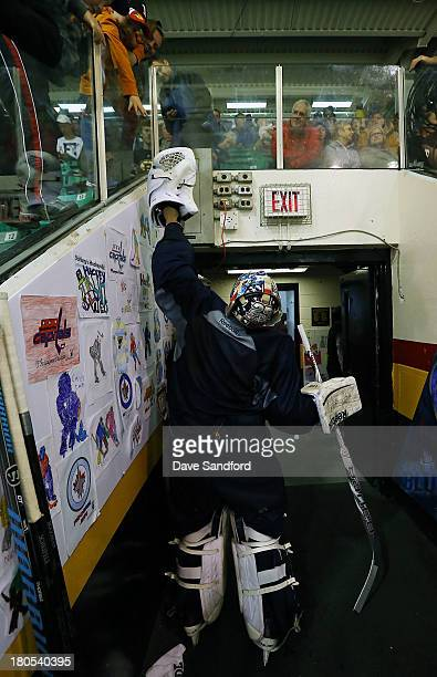 Eric Comrie of the Winnipeg Jets high fives a fan at Yardman Arena during Kraft Hockeyville Day 2 on September 14 2013 in Stirling Ontario Canada