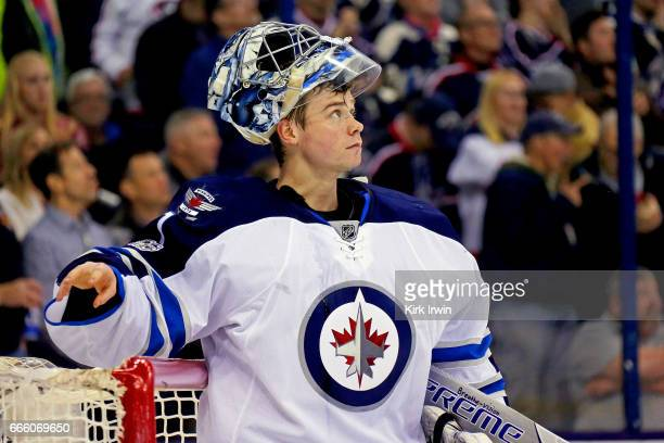 Eric Comrie of the Winnipeg Jets watches a replay after letting in a goal while making his NHL debut during the game against the Columbus Blue...