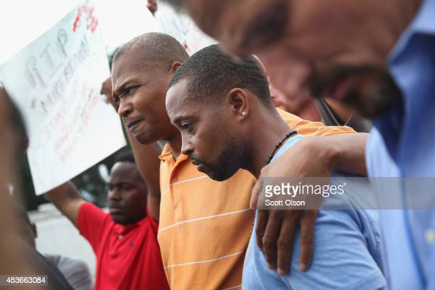 Eric Davis the cousin of Michael Brown comforts Louis Head Brown's stepfather during a press conference outside the police department on August 15...