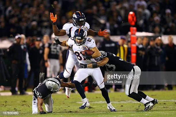 Eric Decker of the Denver Broncos runs with the ball against as he is tackled by Tyvon Branch and Michael Huff of the Oakland Raiders at...