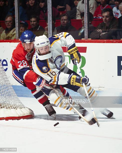 Eric Desjardins of the Montreal Canadiens attempts to get the puck away from Pat Lafontaine of the Buffalo Sabres as he skates around the net with...