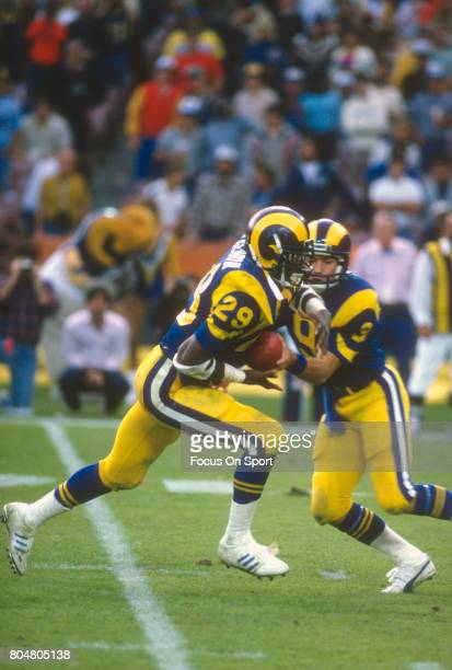 Eric Dickerson of the Los Angeles Rams takes the handoff from quarterback Jeff Kemp against the Houston Oilers during an NFL football game December 9...
