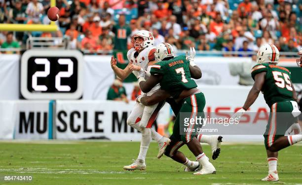 Eric Dungey of the Syracuse Orange has the ball knocked away by Kendrick Norton of the Miami Hurricanes during a game at Sun Life Stadium on October...