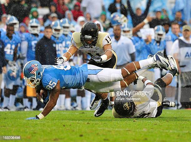 Eric Ebron of the North Carolina Tar Heels makes a diving catch under pressure from Bradley Njoku and Gary Walker of the Idaho Vandals during play at...